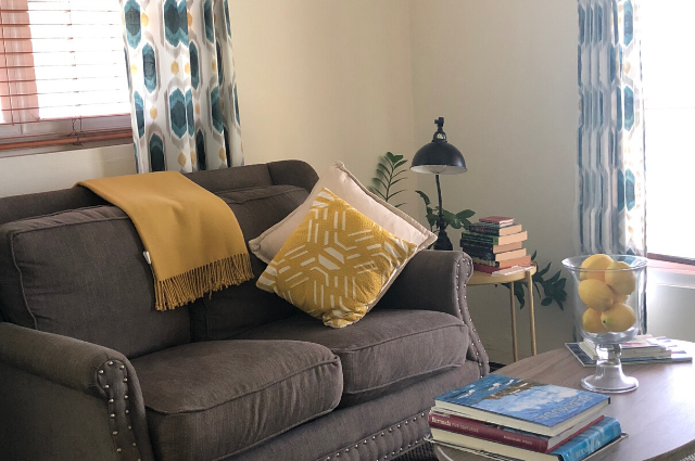 Living room with gray couches and yellow decor